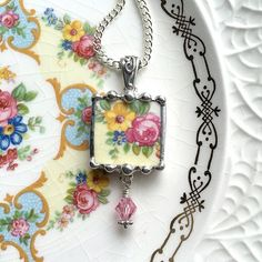 Dishfunctional Designs The original contemporary jewelry handcrafted from broken vintage china...  Artist made broken china jewelry necklace pendant with chain. Handcrafted from: Antique pink cabbage rose porcelain china with Swarovski crystal drop.  Unique square pendant handcrafted from vintage china. Pendant measures approx. 7/8 by 2 including sterling silver bail and hand-beaded drop; silver bead with genuine Swarovski crystal bead.  18 chain included. Arrives gift boxed.  All of my…