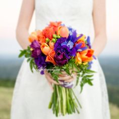 Unstructured wedding bouquet with lisianthus, irises, tulips and trailing jasmine. Image by Tom Hall photography