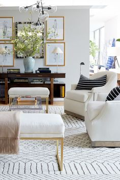 ivory club chairs with a neutral patterned rug and gold accents