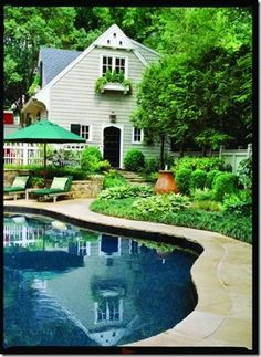 Plants, shrubs, flowers and ground covers to follow the pool line all the way around in a completely filled border.  Via Pretty Old Houses