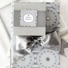 Elegant Silver Packages--Nothing dresses up a gift more than a sophisticated silver scheme. Adhesive diamondlike brads bring dimension to the medallion paper on the large package. The small package swaps wrapping paper for spray glitter -- an easy way to customize boxes you have on hand. For the pretty silver tag, download our free pattern, cut out, and attach with double-stick tape to a silver backing paper of your choice.