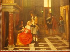 There is an amorous couple by the window and the other one in the foreground, playing cards, that is the two are at the cards table, and it looks like the woman interrupts the game to show her hand to a young man standing next to her. This awkward youth must be Pieter de Hooch's idea of a prodigal son.