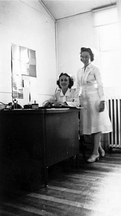 Two army nurses, including Rachel Brower Twiddy (seated), are pictured at the nurses' station on their ward at Fort Ord, California, circa 1942 ~