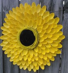 Sunflower --made from 100 spoons, yellow spray paint, an old serving tray, coffee can lid, & some black & yellow pipe cleaners.