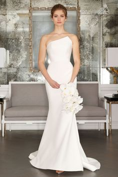 The geometric neckline on this fluted pure white gown adds an edgy touch.