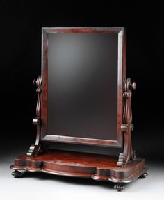 "AN AMERICAN EMPIRE CARVED MAHOGANY GENTLEMAN'S SHAVING MIRROR, THIRD-QUARTER 19TH CENTURY,  the rectangular mirror within a conforming  swivel frame flanked by scrolled supports on a shaped rectangular base and rounded corner plinth, raised on circular lobed feet. Height: 33"" Width: 28 1/4"" Depth: 13 1/4"""