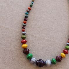 As though a rainbow itself was plucked from the sky and its colors splashed joyously across each bead! You'll find the largest (peach-pit-sized) bead front and center, from which the other beads gradually grow smaller (from grape-sized, to pinky-nail sized, to popcorn kernel size at their smalles...