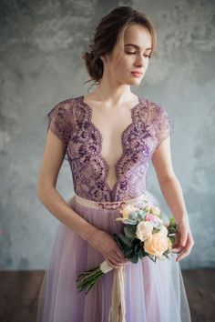 This standout gown features a lavender-hued Chantilly lace bodice with a deep, scalloped V neck. For a multidimensional look, the frothy skirt is crafted from lightweight tulle in two different shades: lilac and ivory. The neckline and the belt are embroidered by hand with rhinestones, crystals, glass beads, and seed beads.
