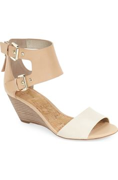 Two-tone leather straps add modern sophistication and versatility to this open-toe sandal set on a stacked wedge heel.
