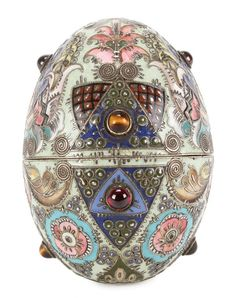 "A RUSSIAN GILDED SILVER GEM SET AND SHADED ENAMEL EASTER EGG, FEDOR RÜCKERT (Friedrich Mauritz Rückert), MOSCOW, 1908-1917. Profusely enameled with geometric and floral ornaments in the Pan Slavic style in various shades against a mint green ground and with applied decorative filigree wires, and set with tiger eye and amethyst cabochons. The interior brightly gilded, hallmarked Moscow, circa 1908-1917, Cyrillic maker's mark ""FR"" and 88 silver standard. Height 7 cm."