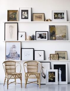 Modern gallery wall of photographs, drawings, and prints on shelves and the floor leaning against the wall - Art Wall Ideas