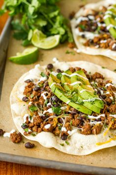 Tostadas Recipe -- homemade tostadas topped with a budget-friendly beef and black bean mixture, shredded cheddar cheese, fresh avocado, cilantro, and a tangy lime crema… SO good, perfect for game day (or weeknight dinner)! #gotortillaland #partyfood (ad) | unsophisticook.com