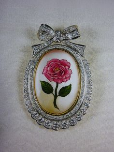 Queen Elizabeth II`s gift to her mother for her 100th birthday. The brooch is made of quartz crystal with a painting on the back of a Queen Elizabeth pink rose, which was a rose named after the Queen Mother, framed in a diamond frame composed of 100 diamonds.