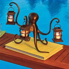 This aluminum octopus is very handy to have around. When you need a little light for ambiance, this aluminum and iron octopus is very handy to have around. Includes 3 lanterns with glass cups for tea lights.