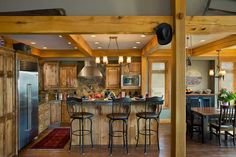 The wood takes center stage in this kitchen. The timbers, which are a mix of white and red oak, complement the knotty alder cabinets and paneled kitchen island. Photo by Roger Wade.