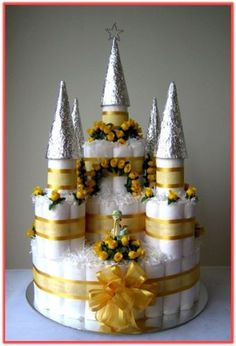 """THE CASTLE"" Nappy Cake (front view) - This charming hand-crafted ""Castle"" Nappy Cake will sure to be a crowd pleaser at any Baby Shower celebration party as well as the perfect baby gift for the new mum and her little prince/princess. The Nappy Cake is presented on a silver corrugated cake board, and it comes wrapped in cellophane with coordinate silk ribbon and hand - tied bow. Code: NC 0431 Price as shown: AUD $119.95"