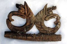 This wood carving depicting two griffins was also found in the grave. It was...