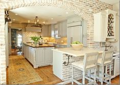 Love this kitchen -- so Louisiana with the exposed and ragged brick wall and the real rug on the kitchen floor.