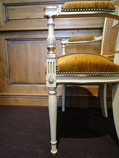 Chaise d'époque Directoire. Caractéritiques : support d'accotoir en forme de balustre, une marguerite inscrite dans un losange à la ceinture du pied, pieds arrière sabre.