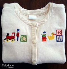 Will this become an heirloom? Baby cardigan sweater embroidered with toys. NellyBelle Designs