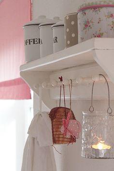 Kapstok als handdoekenrek (gerold bovenop) in badkamer en theelichthouders en badkameraccesoires hangend eraan