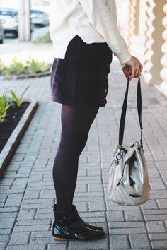 Inspiração fashion pro inverno: ankle boot envernizada preta, meia calça, saia de veludo com botões na frente e bolsa saco.