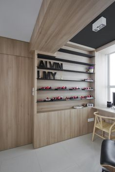 Simple black shelving built into a light wood wall.