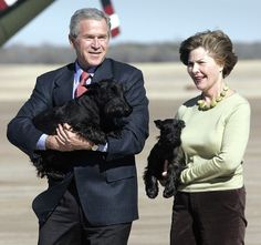 Former president George W. Bush and former first lady Laura Bush carry their Scottish terriers Barney and Miss Beazley.