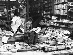 """A boy sits amid the ruins of a London bookshop following an air raid on October 8, 1940,   reading a book titled """"The History of London.""""   http://scrivi.10righedailibri.it/"""