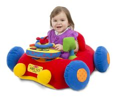 "This sit-in play car lets little ones rev up and take off for fun! With a clicking steering wheel, light-up dashboard, rear-view mirror, and an engine that plays music when the key is inserted, this activity toy will keep your child happily occupied while building physical, cognitive, and social skills. There's even a cup holder on the side and a mesh ""trunk"" in the rear to take favorite toys along for the ride!"