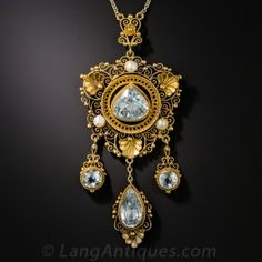 This fanciful Victorian pendant necklace glows with a captivating quartet of multi-shaped aquamarine gemstones. Centering on a voluptuous pear shape, the intricately designed jewel is adorned with finely granulated scallop shell motifs, exquisite filigree work and a trio of lustrous natural pearls supporting three dangling drops. An exceptional antique adornment, expertly hand-fabricated in richly patinated 18K yellow gold. 2 1/2 by just over 1 inch. The original chain measures 16 1/2…