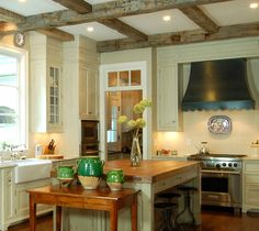 cute country range hood - exposed beams, nice cabinets, butcher block island top