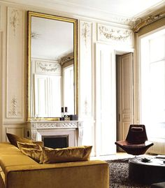 Love the oversized gold mirror paired with the rich golden yellow velvet sofa.