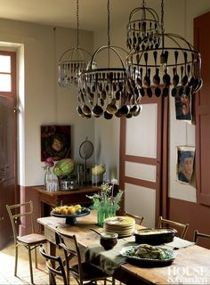 Brocante single-tiered chandeliers made from antique spoons, ladles, and forks decorate a rustic dining room. #HouseandGarden