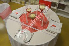 Voici une décoration de tables sur le thème de Noël. On a : une nappe en papier blanc, un carré d'intissé comme centre de table (60cm x 60cm), un ruban satin et son ruban diamant, des petits diamants et des perles de pluie transparents, des bougies flambeaux, des bougeoirs sur pieds avec une rose ivoire à l'intérieur et pour les chaises, celles-ci sont habillés avec des housses de chaises rondes blanches (tout dépend du type de chaise que vous avez) et des noeuds satin ou organza rouge.