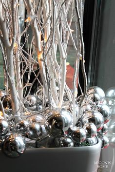 Spray paint twigs and sticks white, wrap twinkle lights around them and cover the bottom of your urn with silver balls.