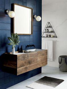 déco de la salle de bain moderne avec peinture murale en bleu foncé et blanc, carrelage à design marbre blanc, étagère en fer et forme triangulaire