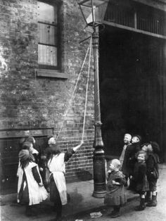 A group of East End kids playing in the street, swinging from the gas streetlamp, London, c.1900.