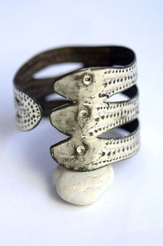 BRASLE FE DAMBALLAH - This snake cuff is hand chiseled in an historic, Haitian ateliér from upcycled steel. Gilded with white gold at Mi Ossa.