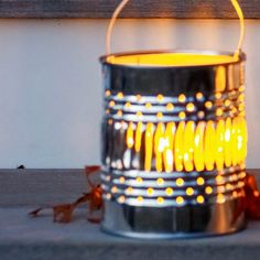 To make decorative luminaries, drill holes in pint-size cans, making a pattern. Place a votive candle in each can. | Photo: Tina Rupp