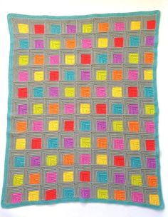 ** This pattern is written in English. No other languages are available ** This stunning mitred square blanket will add a pop of colour to your home. The textured stitches and mitred squares create the illusion of a 3D effect making it visually interesting and very touchable.