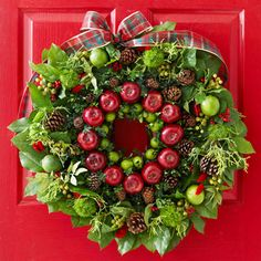 This bountiful Christmas wreath is actually two -- a smaller wreath form adorned with apples, Key limes, pinecones, and boxwood fits perfectly inside a larger wreath decorated with limes, lemon leaves, berries, cypress, thistle, and bells of Ireland.