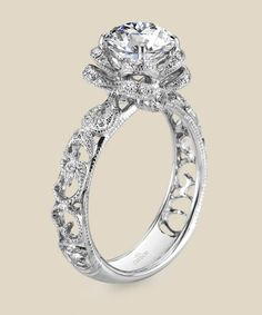 This vintage floral inspired design is anything but your typical engagement ring as milgrain etched scrolls curl and climb towards a round-cut diamond emerging from a blossoming flower. Diamond Info: 52-RD 0.27 CTS Fits center stone size RD: 6.5-7.0 MM GUIDE Center stone not included.