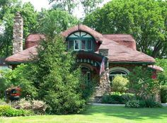 The unusual bungalow style stone cottage pictured below was clearly in-  fluenced by English cottage design.     Located in the Hyde Park area of Cincinnati,  Ohio,  USA,  it features half-timbering above the upper story windows and a distinctive  wood  shingle  roof  designed  to  emulate  a thatched roof.
