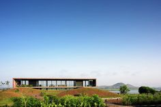 Photos by Hemant Patil via ArchDaily. Composed of a cuboid concrete box with glass walls, and gently placed on an undulating plateau in India's Sahyadri mountain range, in the...