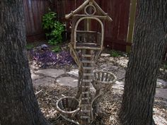 Composed of various woods, including cedar, birch and vine, this bird feeder stands 46 tall. It has 2 plant holders, and twisted vine detail. Perfect