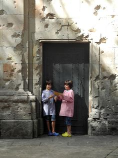 Plaça De Sant Felip Neri, Barcelona. School children playing in a courtyard heavily bombed during the Spanish Civil War (killing around 40 children from the same school). The bomb damaged walls also bear the mark of gun shots as members of the Resistance were lined up against this wall and shot. Now, in this same space, the sun shines, the fountain flows and the children play.  Photo taken by Lucy Churchill