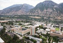 An aerial view from above of the Brigham Young University Campus with the scenic site of the tall mountains (part of the wasatch front and mountain range), on the edge of the east side of the city limits.