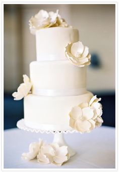 Our beautiful Magnolias (MAG) on a three-tier white cake