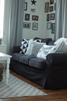 Harmaa sohva sohvatyynyineen